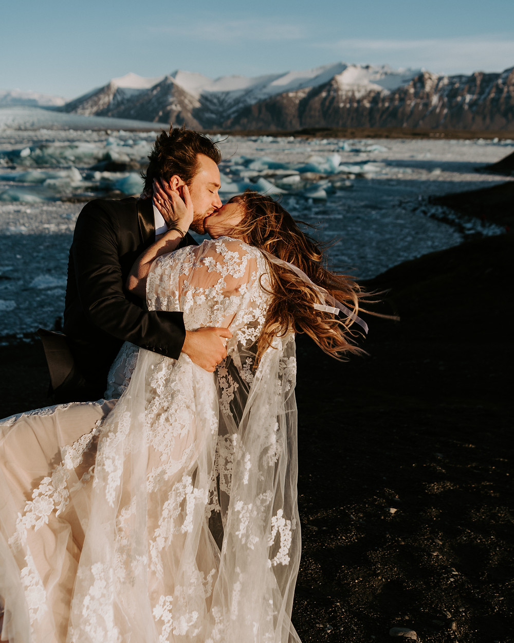 Man and woman kissing on wedding day with glacier background in Iceland