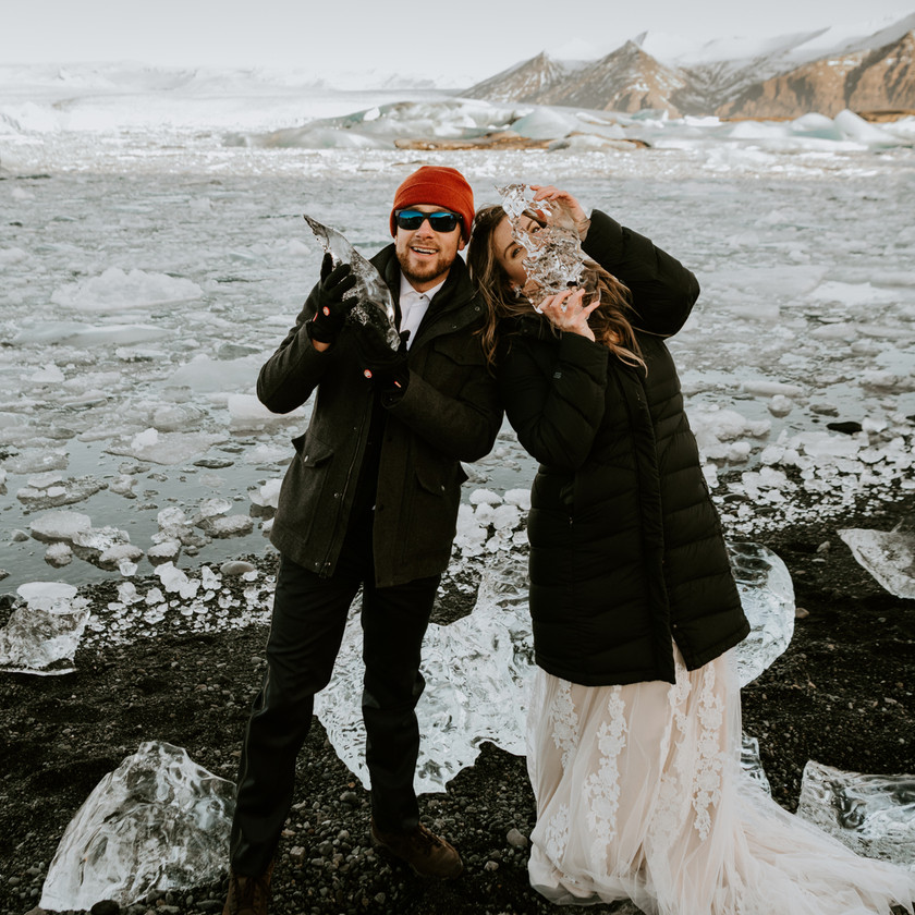 Husband and wife playing with ice in Iceland during their wedding photo shoot