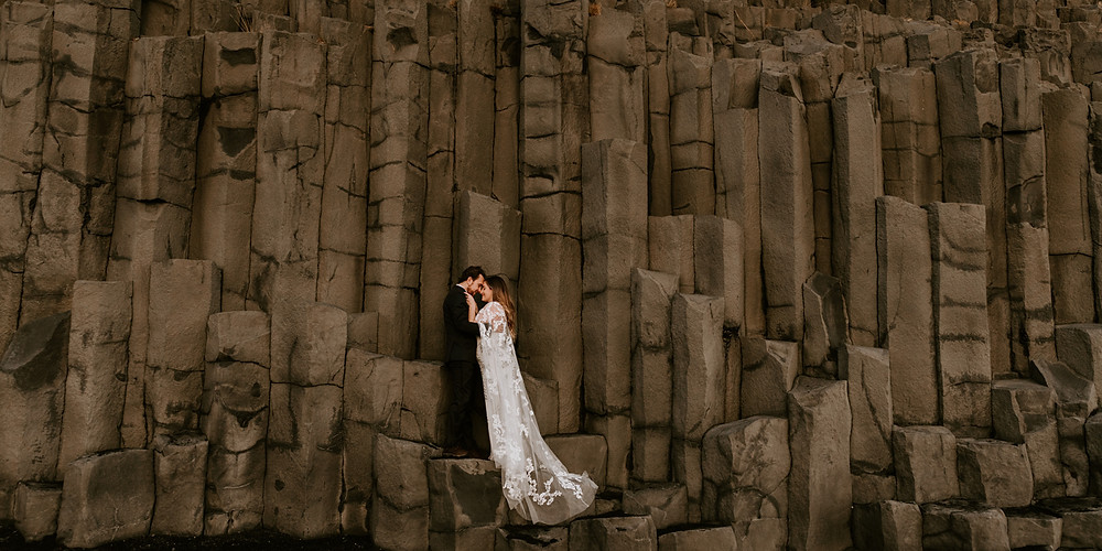 Man and Woman embracing amongst rocks on Reynisfjara, Black Sand Beach in Iceland