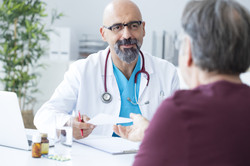male doc talking to patient smiling