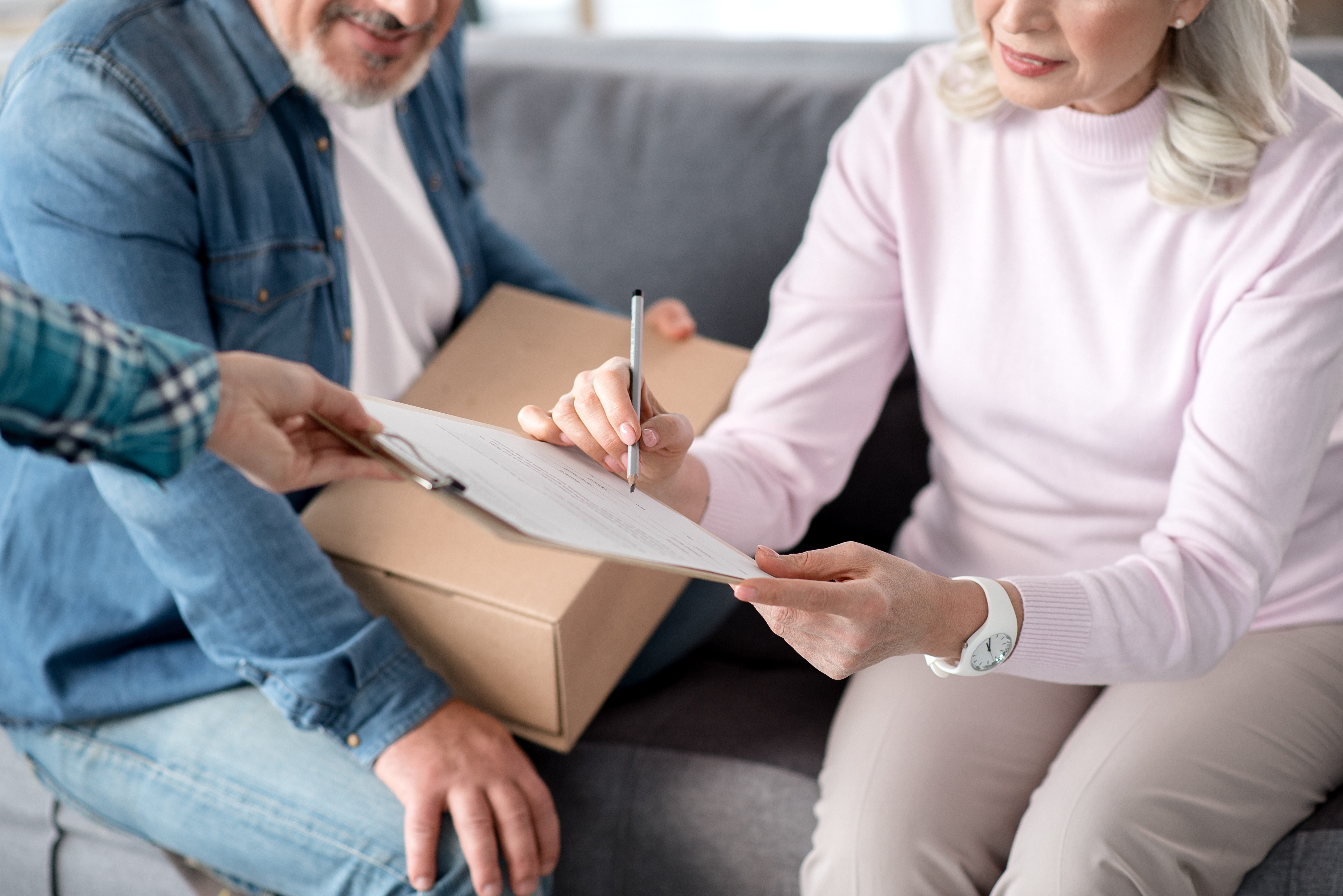 elderly couple signing for package