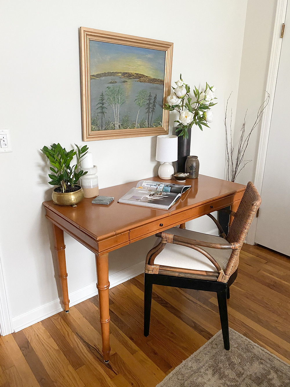 small office with vintage painting and rattan chair