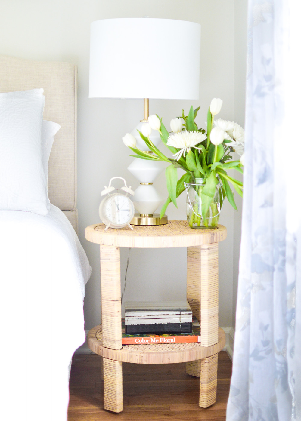 Beautiful bedroom vignette with rattan side table, linen headboard and tulips in a vase.