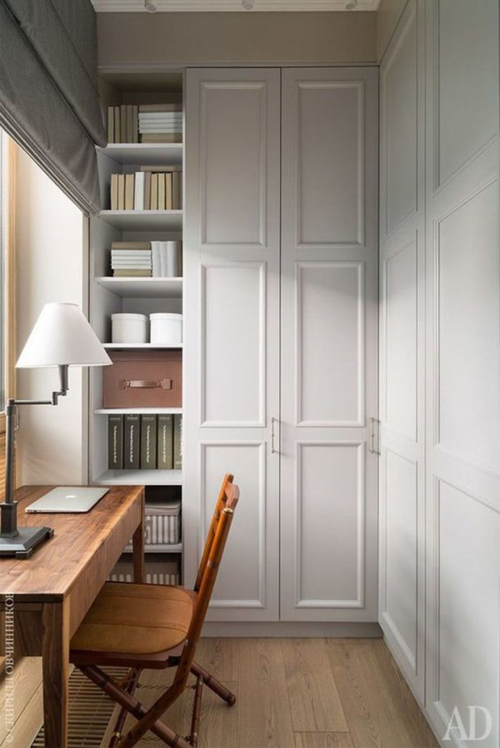 Desk in a library nook designed by Pufik Interiors featuring an antique desk and vintage chair