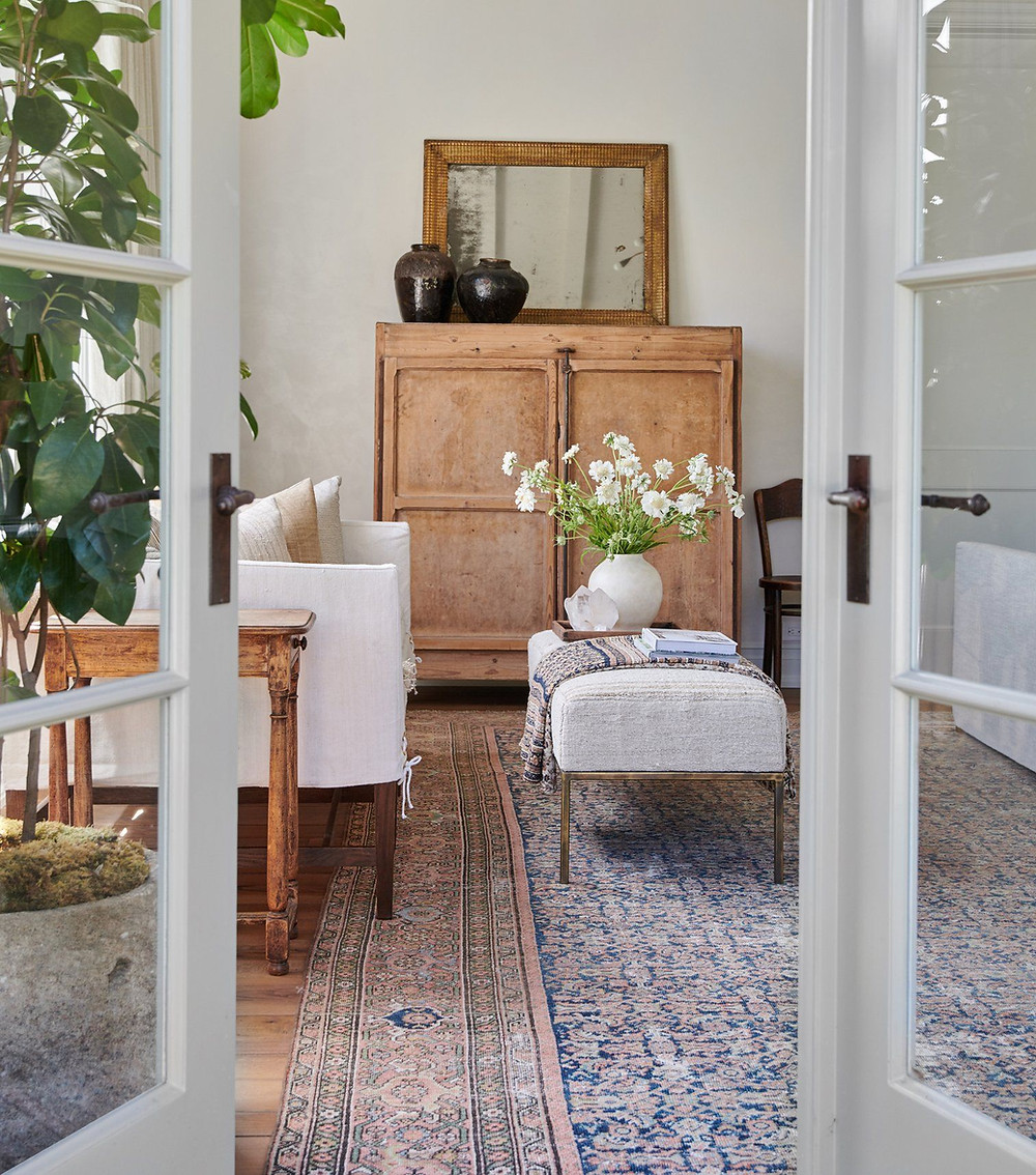 Amber Interiors Made for Living book cover sitting area with gorgeous natural wood detail, a blue and white vinatage rug, slipcover sofa, found pots and antique chairs.