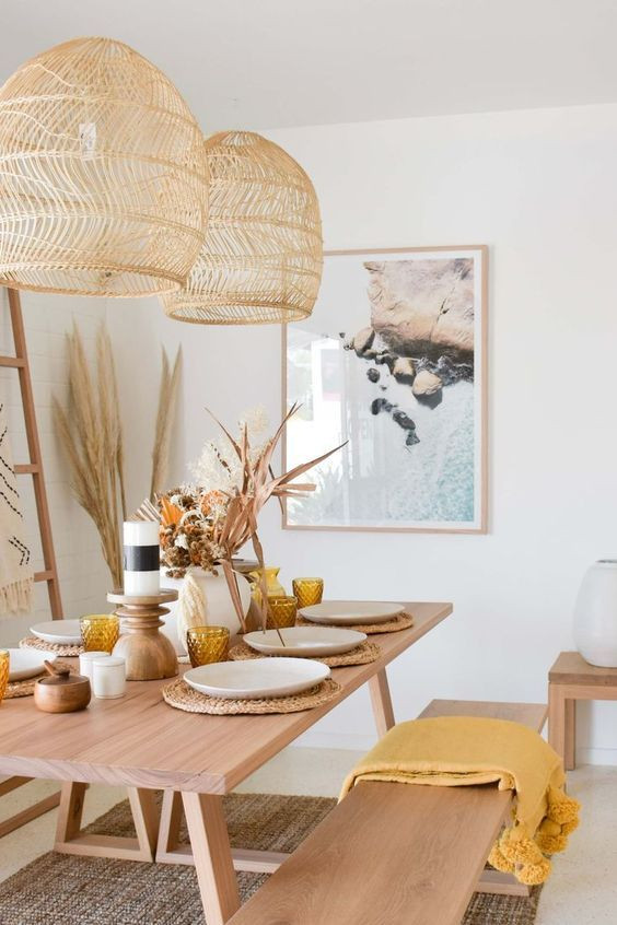 Boho dining room design with rattan pendant lights, mustard color palette, beautiful beach art print, and pampas grass