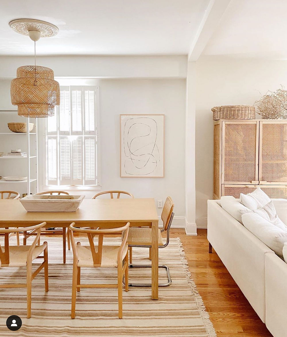 Living room design with rattan including the Ikea sinnerlig light, a jute rug, wishbone chairs, white walls, and more!