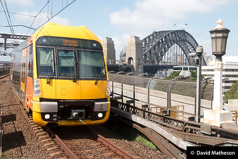 Waratah train Set A72 approaching Milsons Point station with the Sydney Harbour Bridge in the background, 18 February 2017.