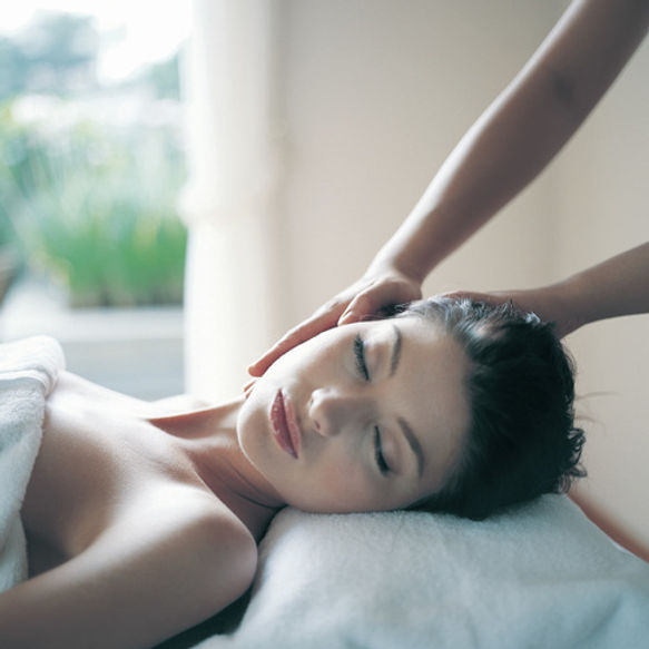 A woman is resting peacefully on a massage table while her massage therapist gently cradles her head.