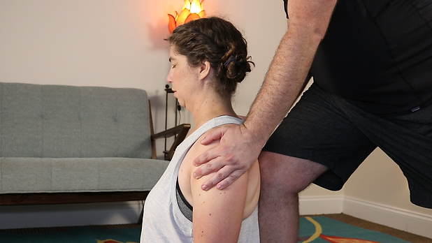 coFLO modern partner massage techniques. Kerri is receiving a seated massage from John in the comfort of their home.