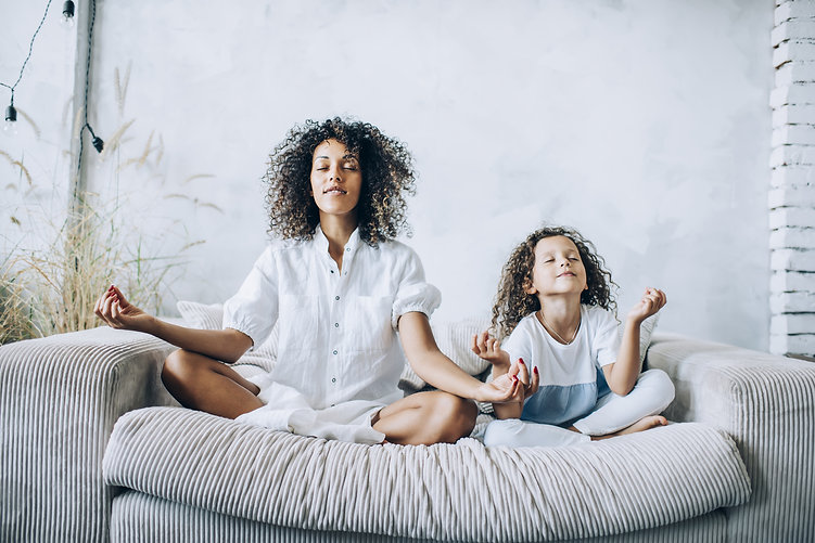 parent and child meditating by the windo