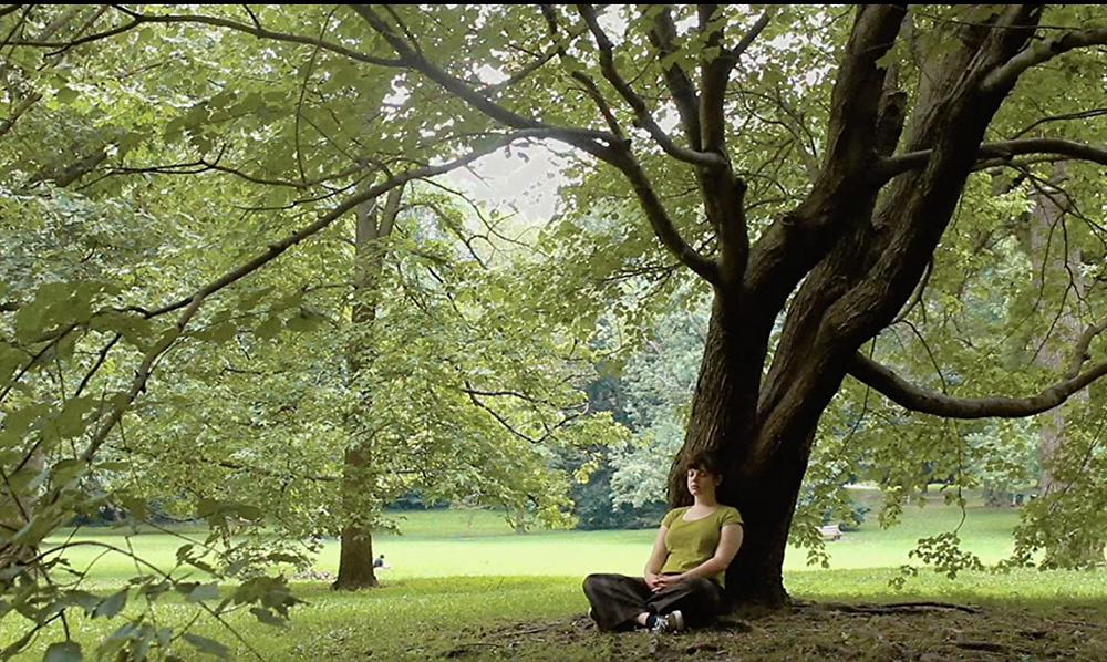 Still image from Kaleidoscope in which Grace Conley's character sits by a tree.