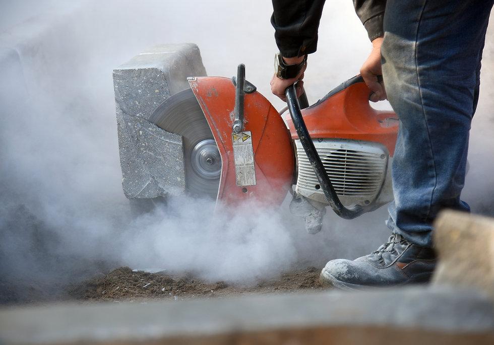 A worker cuts concrete curb circular saw