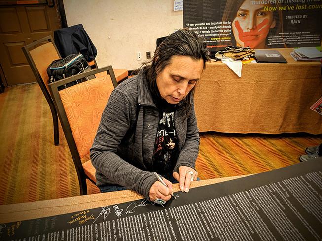 Winona LaDuke signs the Wolf Treaty
