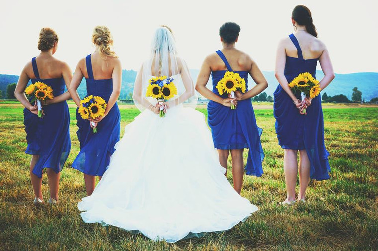 bride and bridesmaid holding sunflower