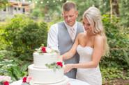 Groom and Bride slicing wedding cake