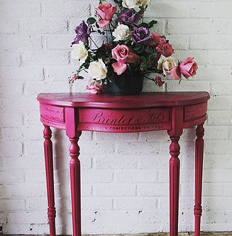 bright pink table with flowers in hallway