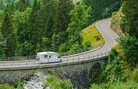 A campervan travelling on a road through a forest.