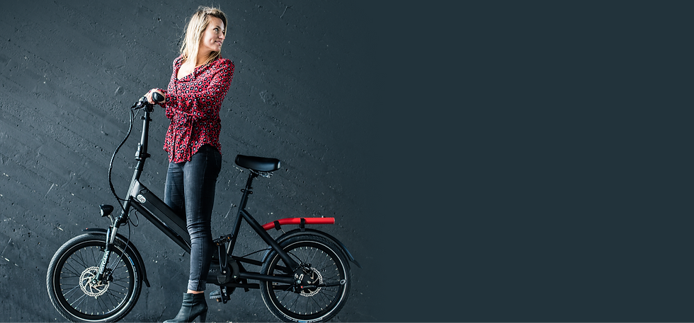 A blonde woman standing with the bike, looking over her left shoulder.