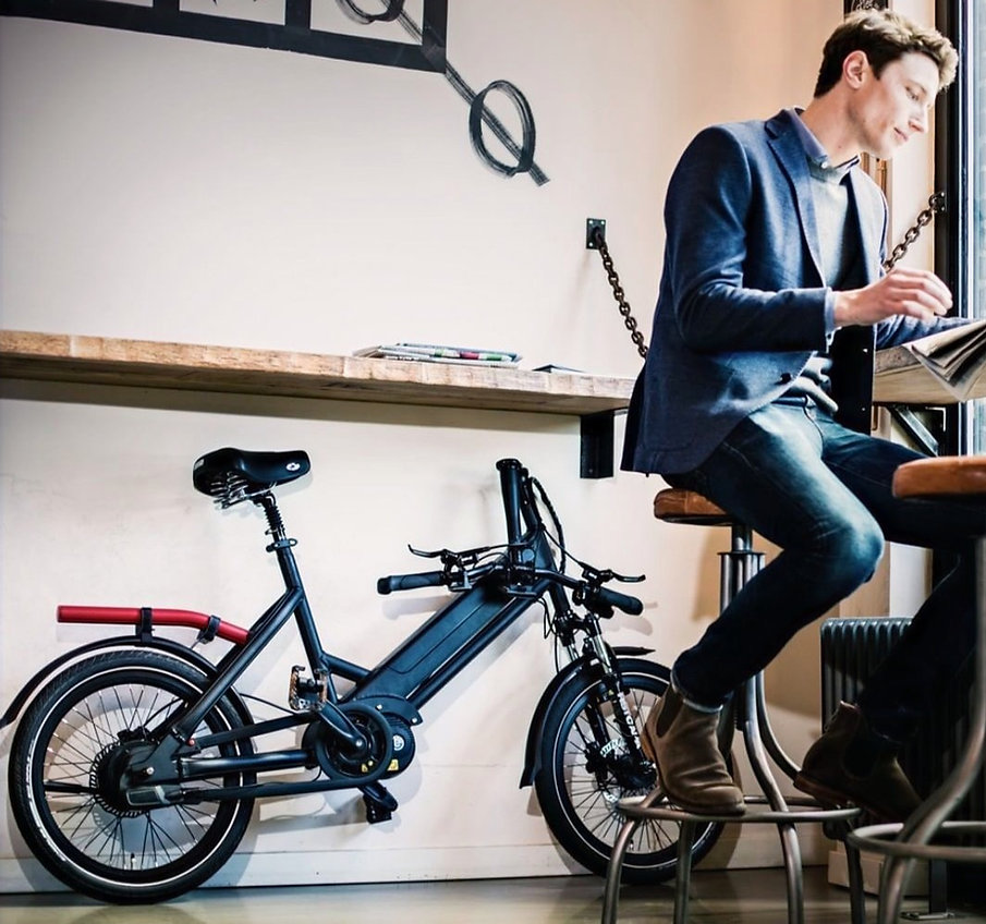 An image of a man reading a newspaper with the compact e-bike folded under a shelf.