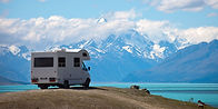 A camper van overlooking a blue lake with mountains in the background.