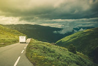 A camper van moving away from us on the open road in rolling hills