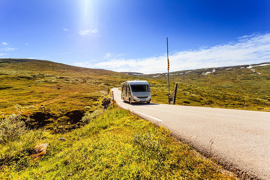 A caravan on a road in a landscape on a sunny day.