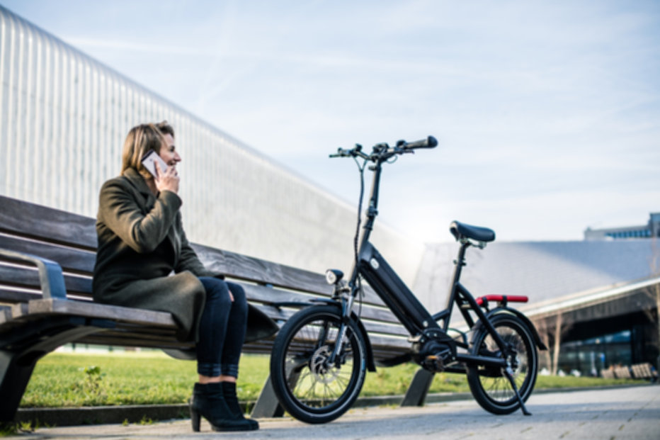 A woman sitting on a park bench talking on the phone with the e-bike in the foreground.