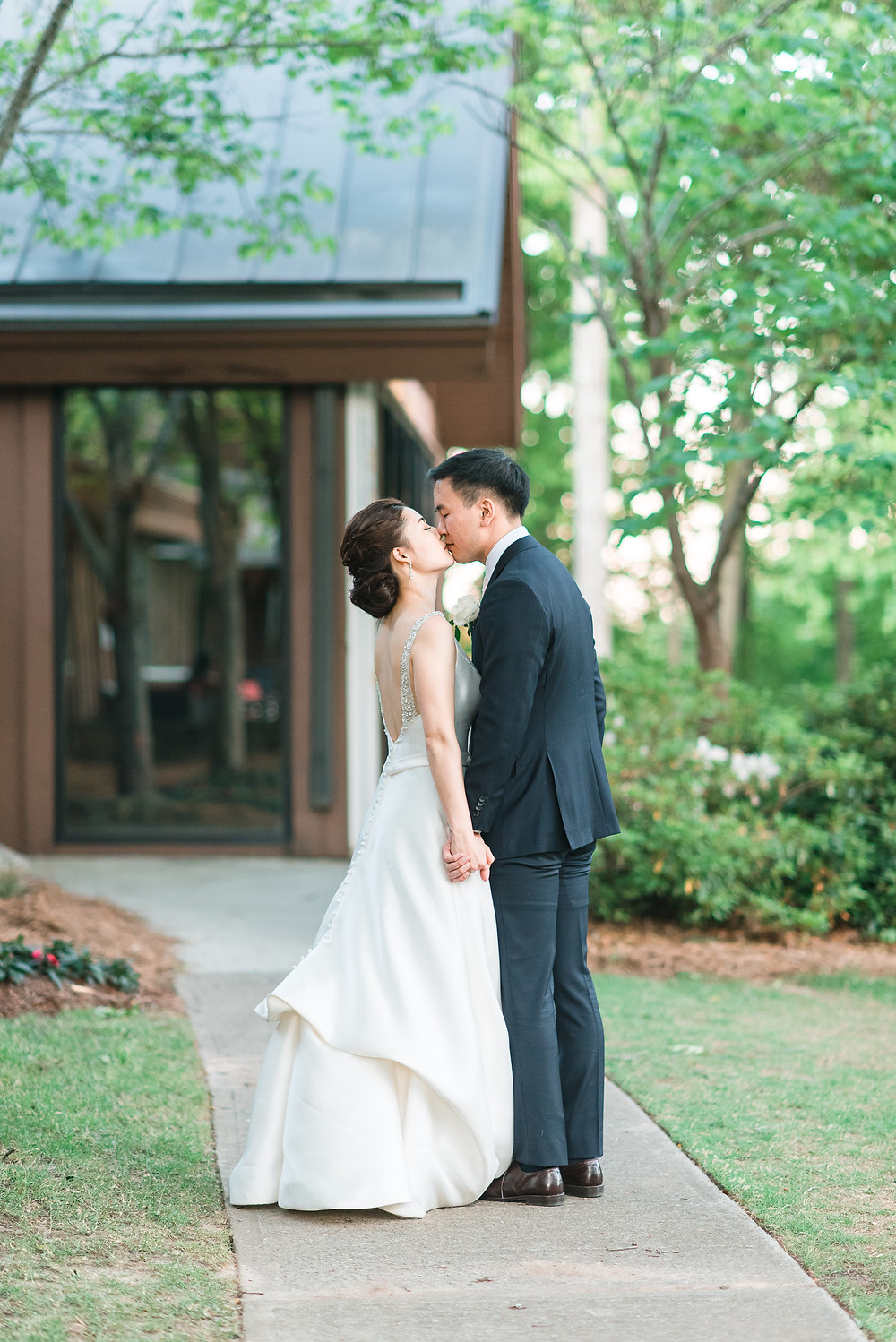 a newlywed couple kissing on the golf course of country club of the south photographed by destination wedding photographer