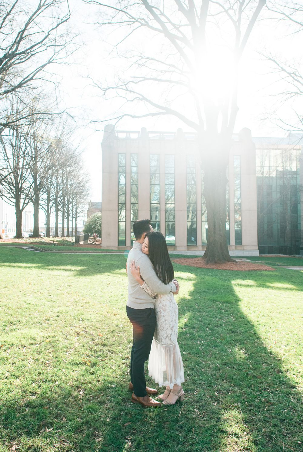 engagement session in downtown atlanta asian couple kissing forehead with white dress and j crew sweater candid photo hug