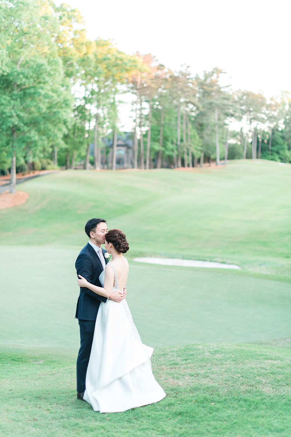 a newlywed couple kissing on the golf course of country club of the south