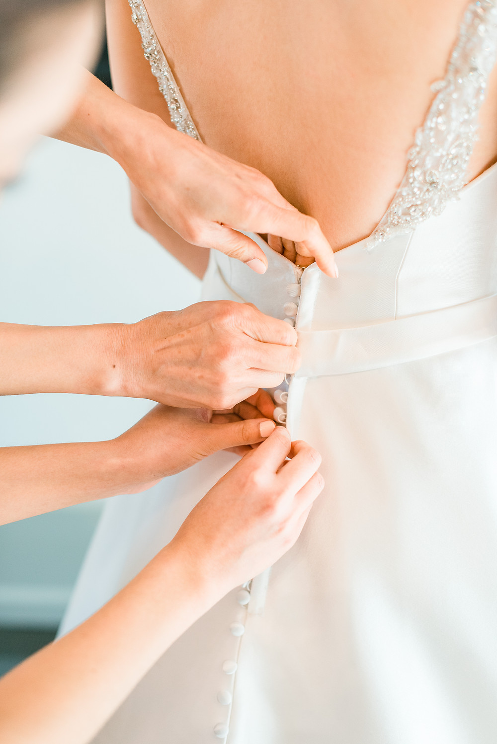 brides putting her wedding dress on with moms help at the country club of the south