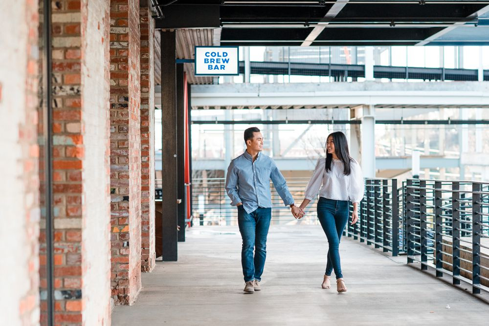 engagement session in downtown atlanta asian couple kissing forehead with white dress and j crew sweater white columns building cold brew bar