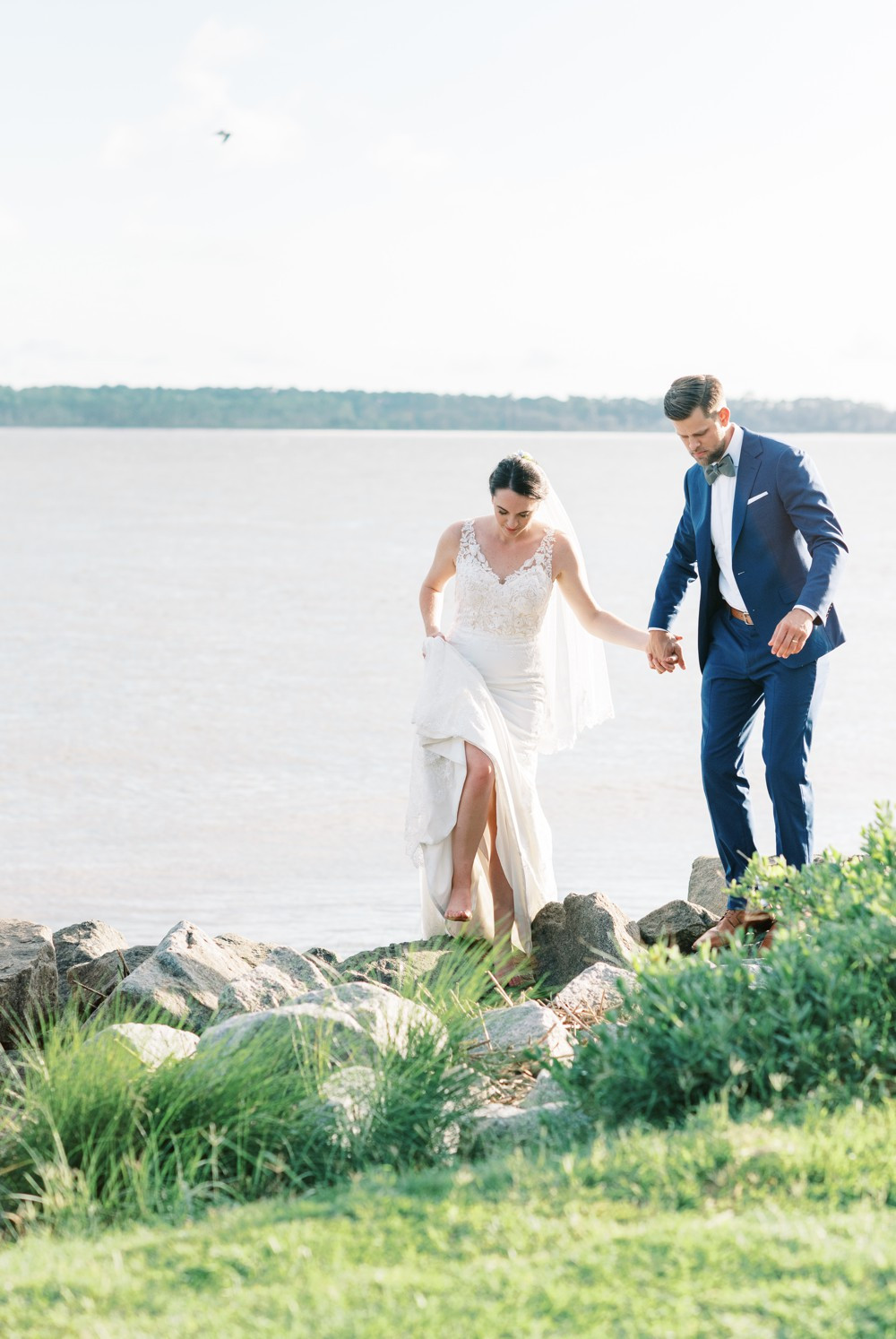 A Destination Wedding at St. Simons Island bride and groom holding hands on the beach rock