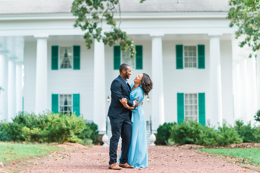 happy couple laughing in front of a plantation in an engagement session in downtown roswell