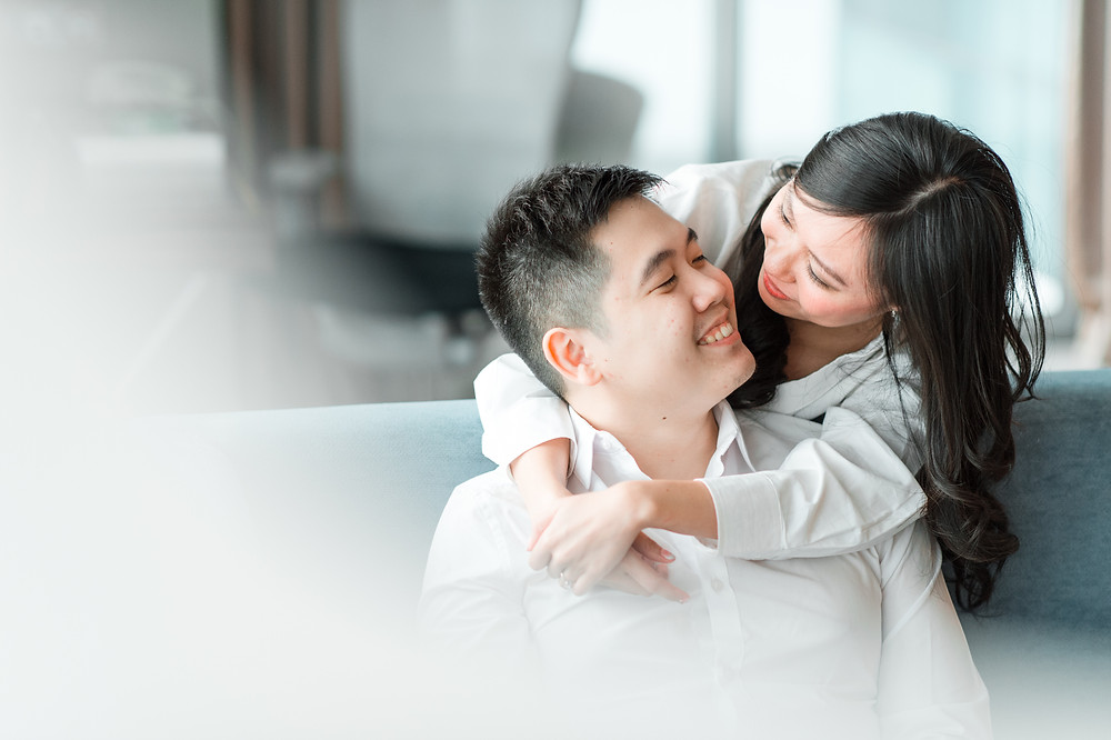 An asian couple snuggles at their house in Jakarta for their prewedding photo