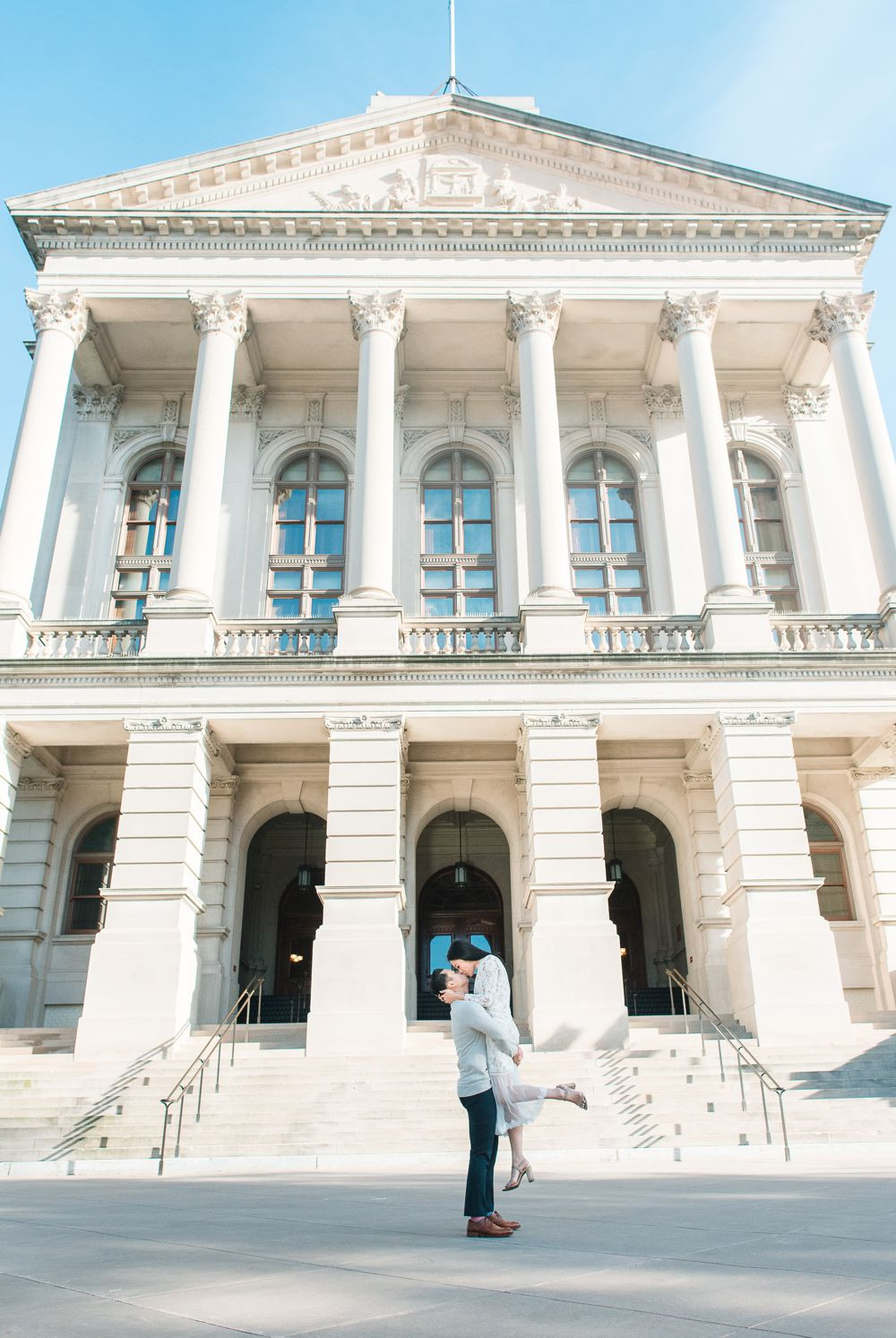 engagement session in downtown atlanta asian couple kissing forehead with white dress and j crew sweater white columns building dc lincoln memorial area