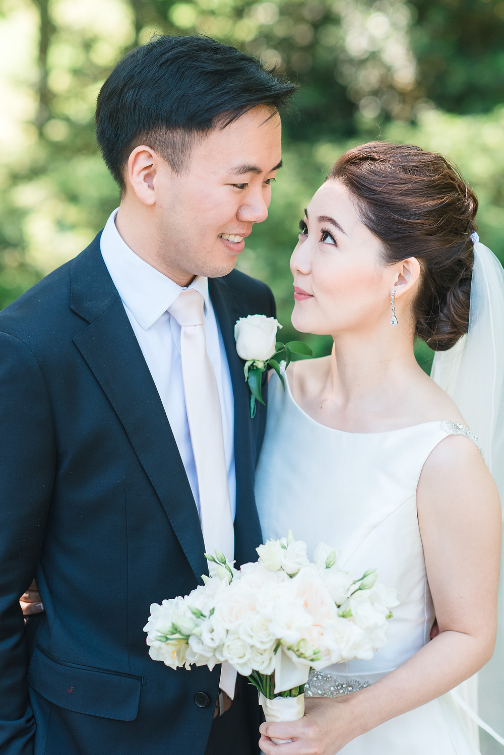a bride and groom with blush bridal bouquet looking at each other lovingly at the country club of the south photographed by glorious moments photography