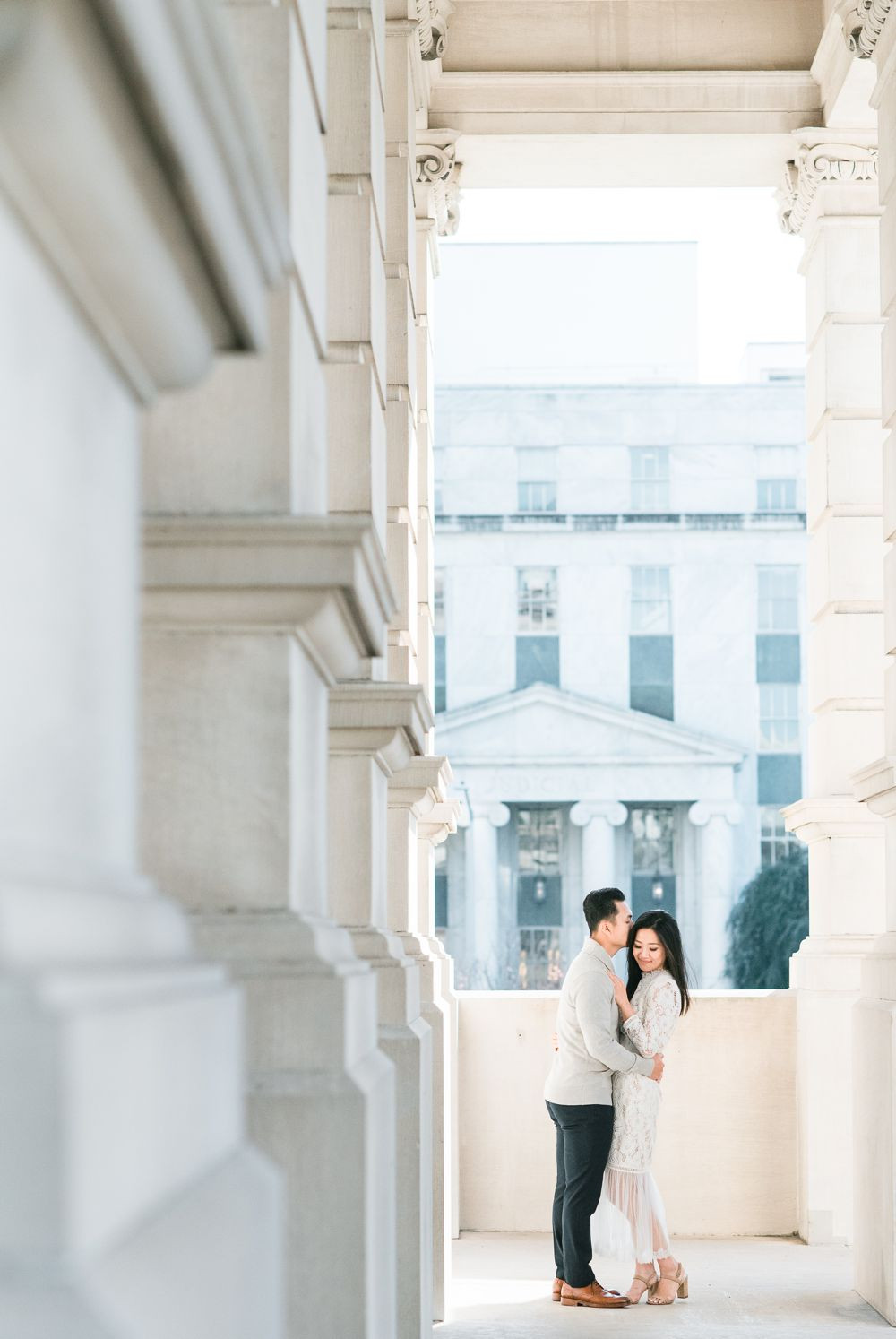 engagement session in downtown atlanta asian couple kissing forehead with white dress and j crew sweater white columns building georgia state capitol