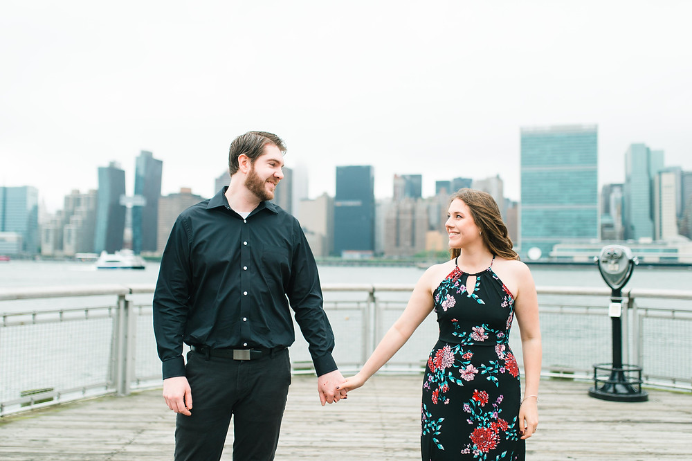 a couple that is so in love in front of NYC skyline holding hand at Gantry Plaza State Park