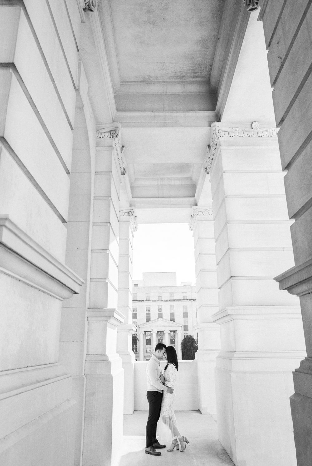 engagement session in downtown atlanta asian couple kissing forehead with white dress and j crew sweater white column building