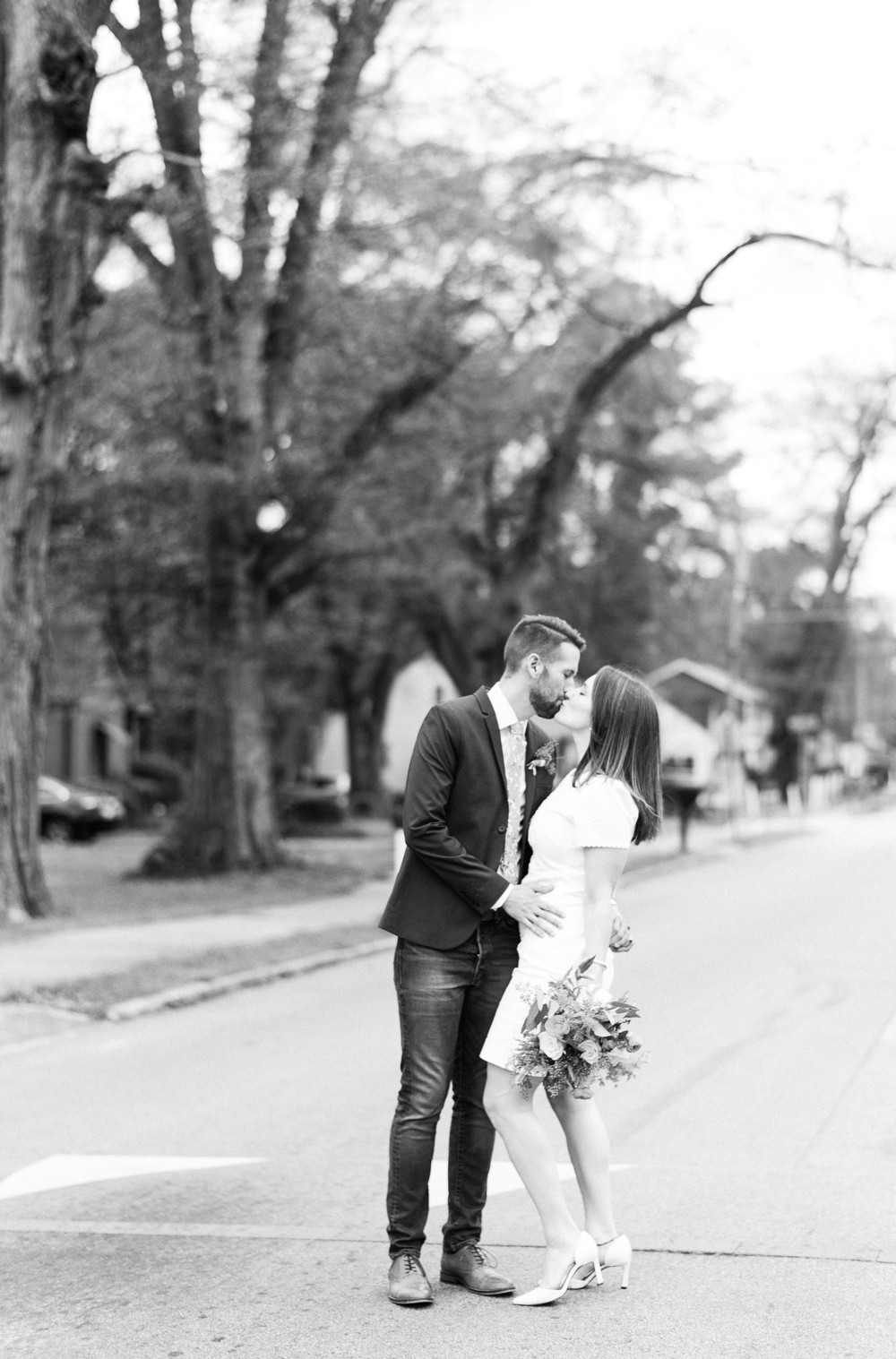 a bride and groom wearing nice dresses getting married kissing in the middle of the road in the midst of covid-19