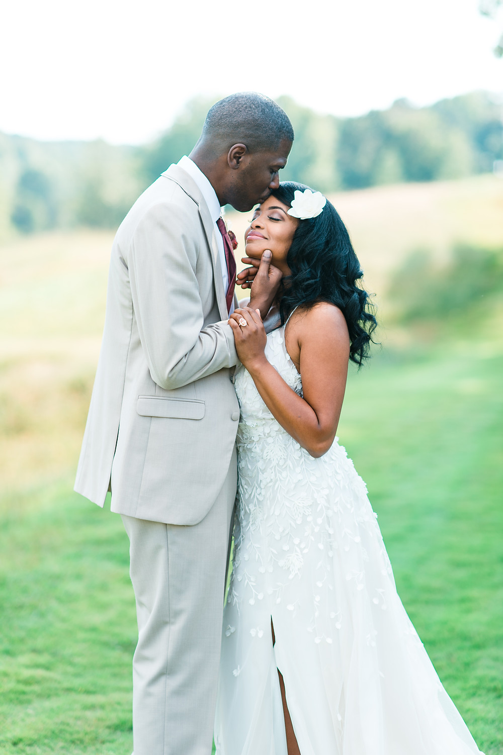 A groom kissed her bride on the forehead at The Greystone Estate