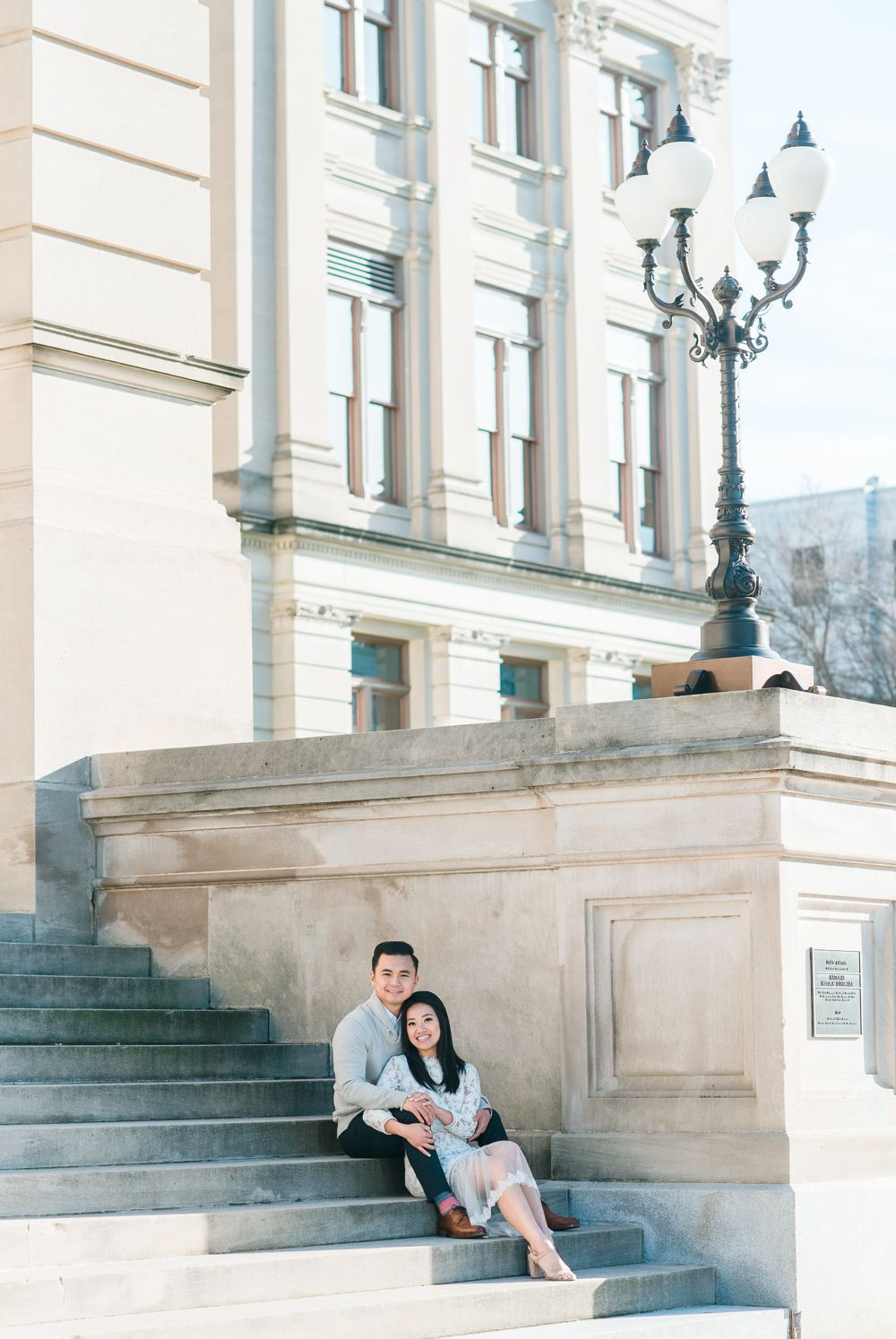 engagement session in downtown atlanta asian couple kissing forehead with white dress and j crew sweater white columns building atlanta