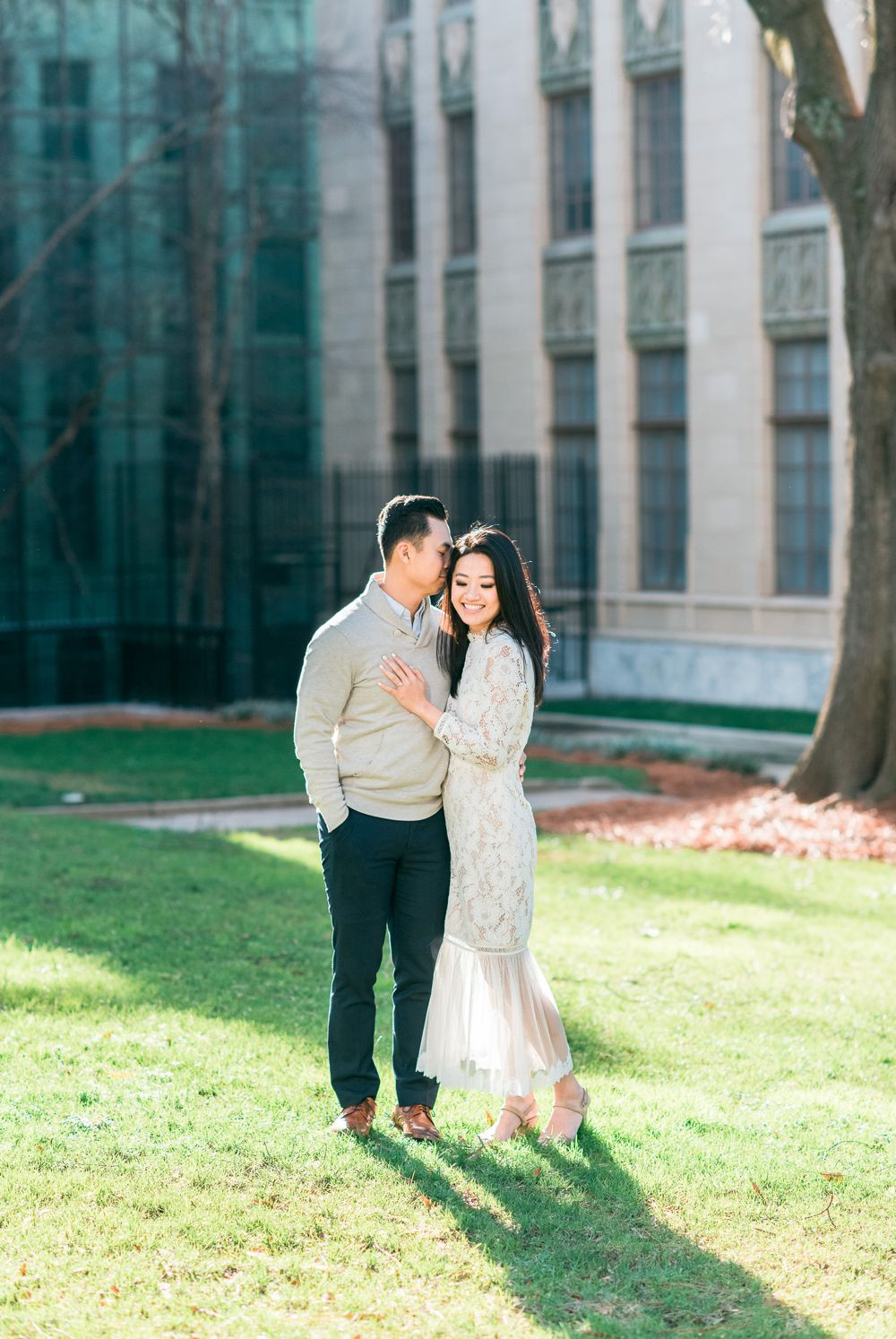 engagement session in downtown atlanta asian couple kissing forehead with white dress and j crew sweater candid photo