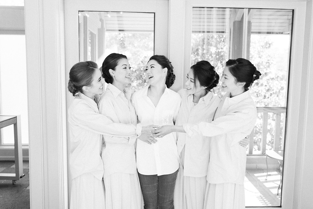 brides getting ready with the bridesmaids with blush robes