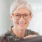 Femme d'âge mûr aux cheveux gris courts et portant des lunettes, fixant la caméra