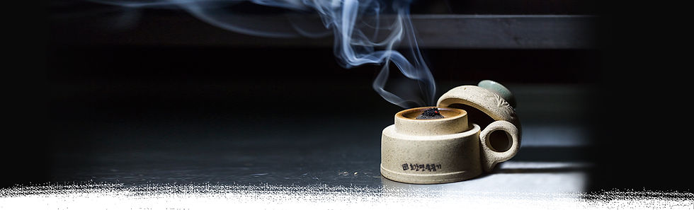Moxa jar with a burning moxa cone on a black background