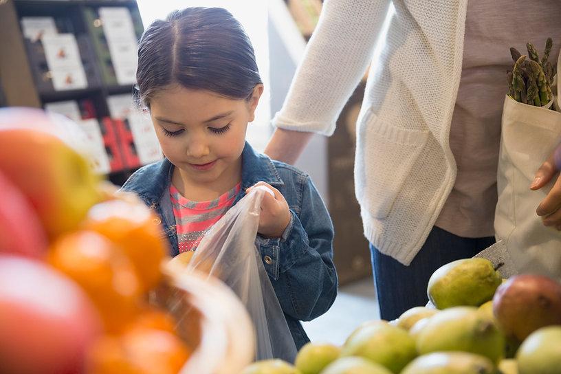 Uma criança do sexo feminino, com cerca de 5 anos de idade, escolhe frutas num mercado.