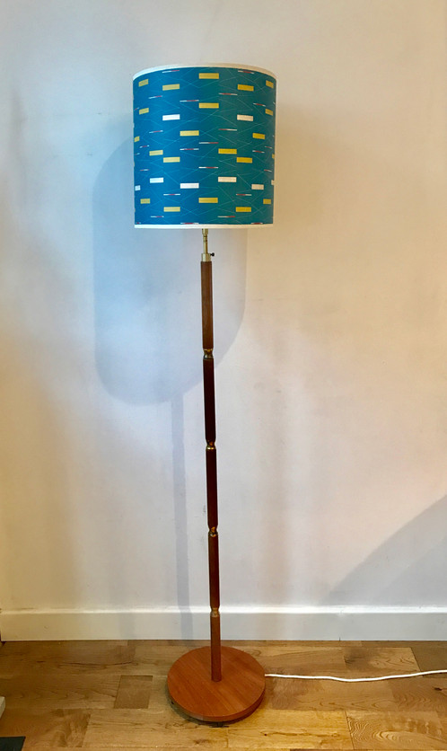 A nice danish floor lamp made from teak with brass details the brass has some tarnish consistent with age and the height is adjustable